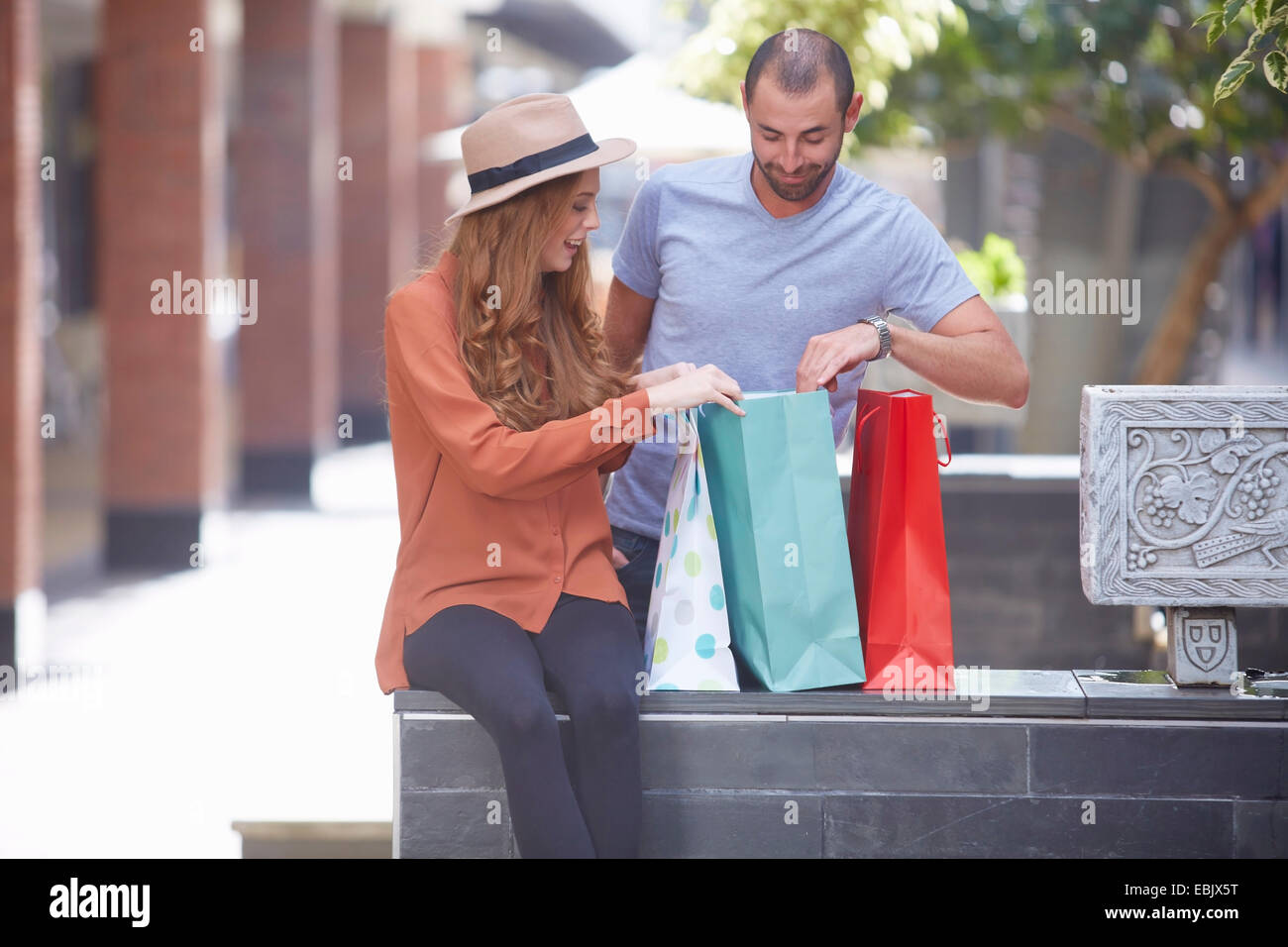 Young woman sitting on wall with shopping bags, man looking in bags - Stock Image