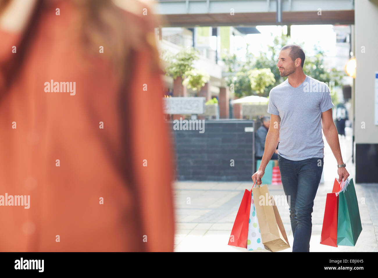 Mid adult man holding shopping bags, walking behind woman - Stock Image