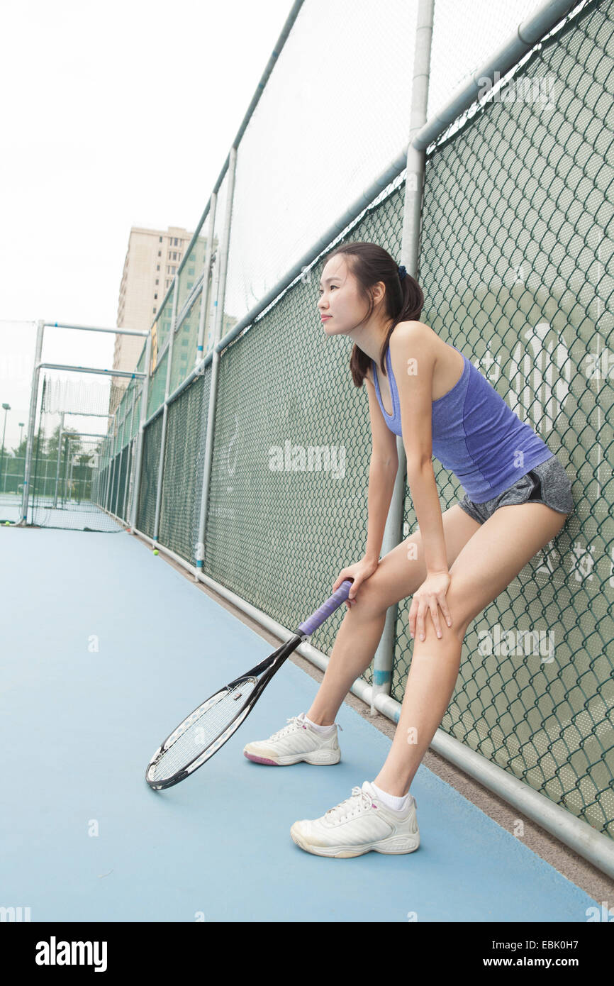 Young female tennis player leaning against fence on tennis court - Stock Image