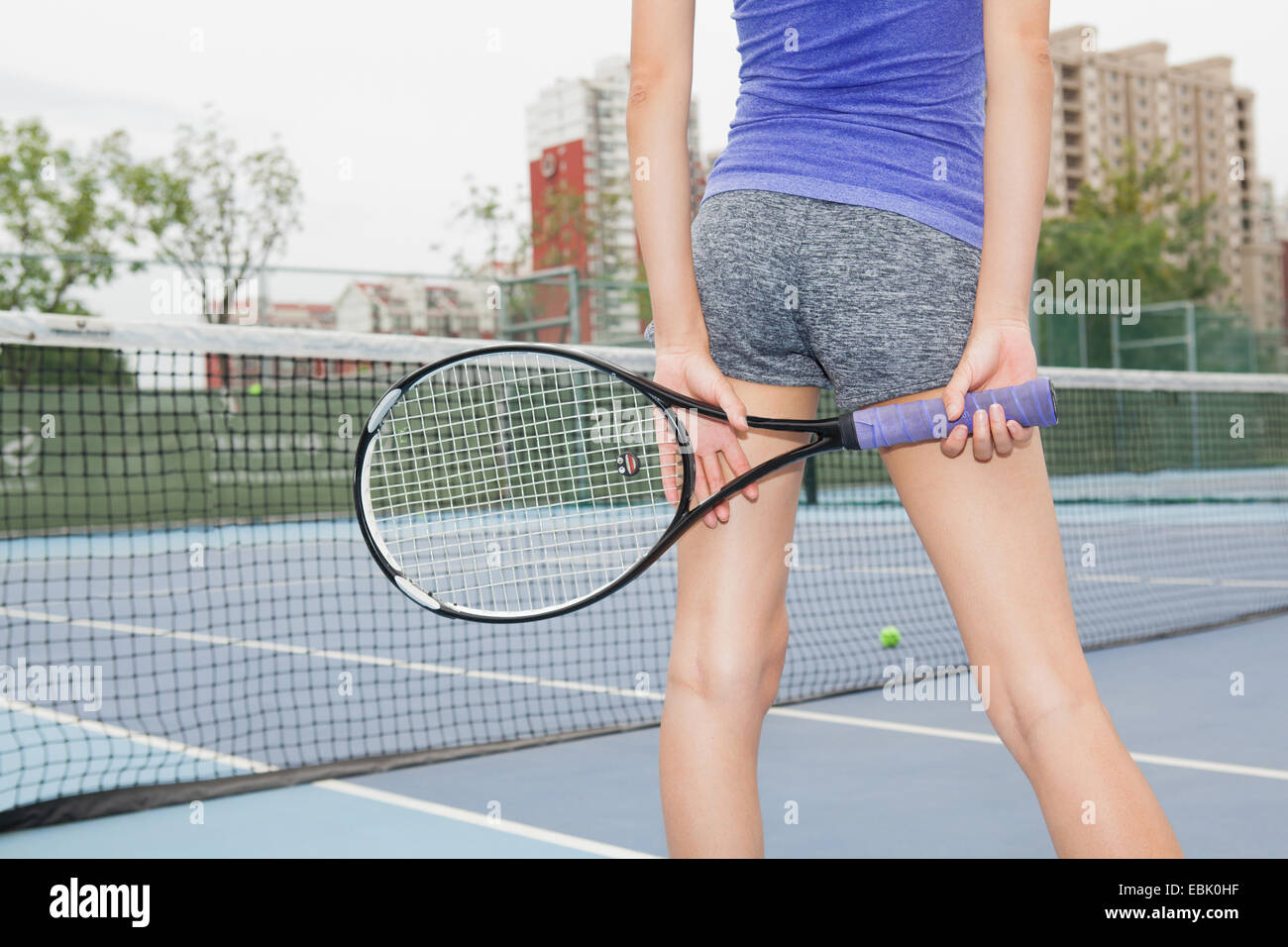 Cropped rear view of young female tennis player on tennis court - Stock Image