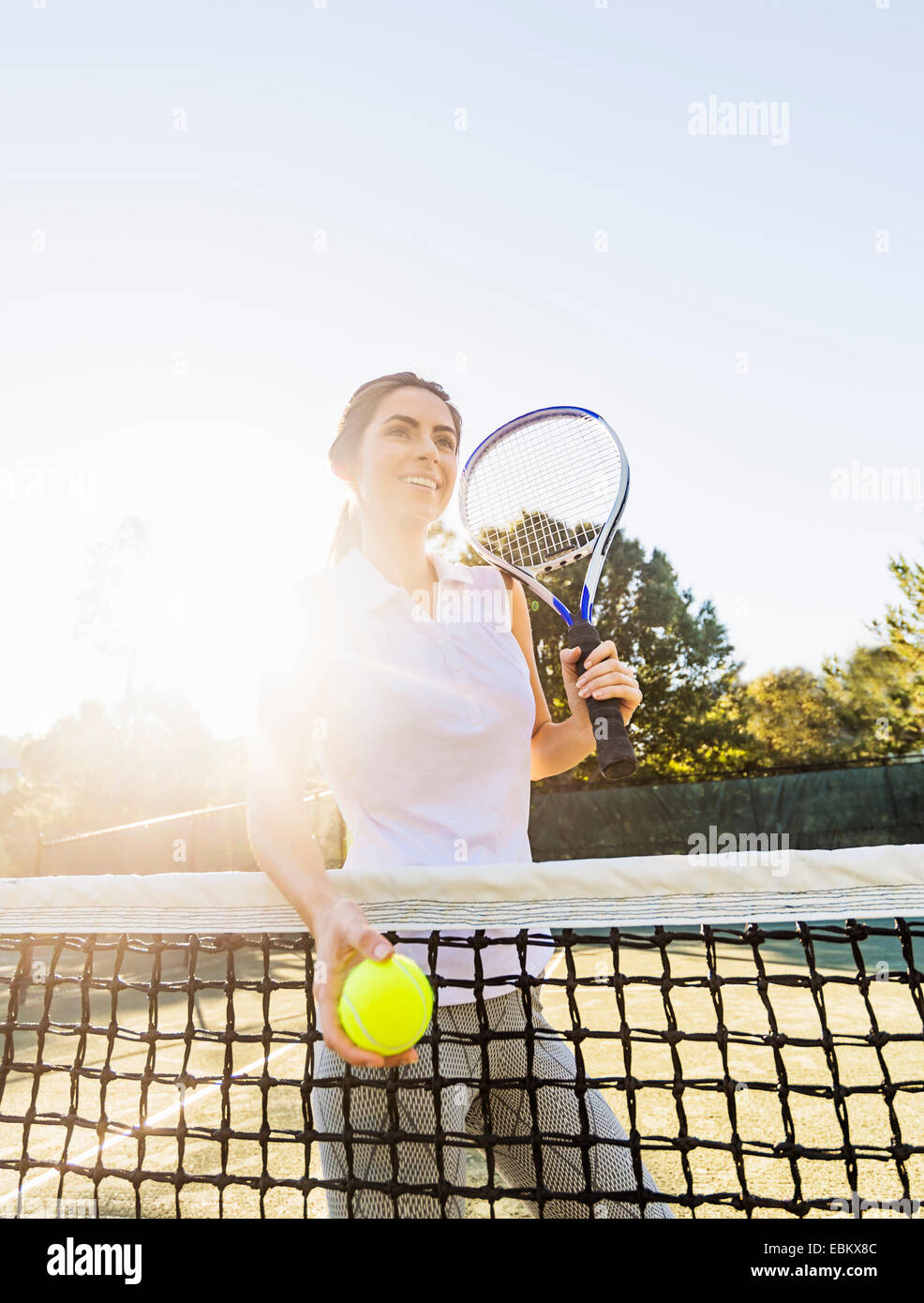USA, Florida, Jupiter, Portrait of young woman standing by net, holding tennis ball and tennis racket - Stock Image
