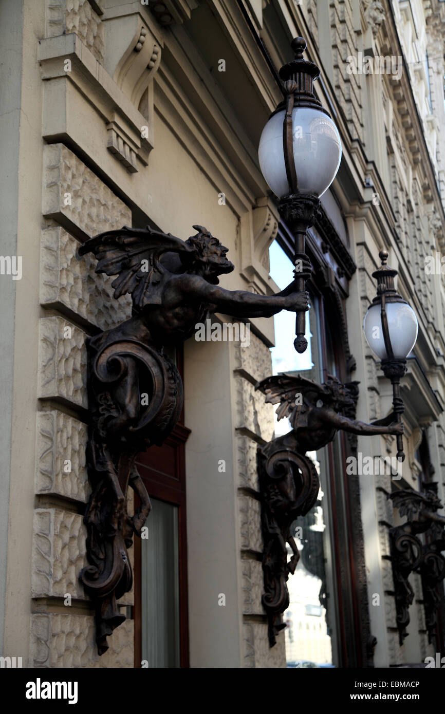 Upright picture of statues or decorations of mythical creatures holding a lamp - Stock Image