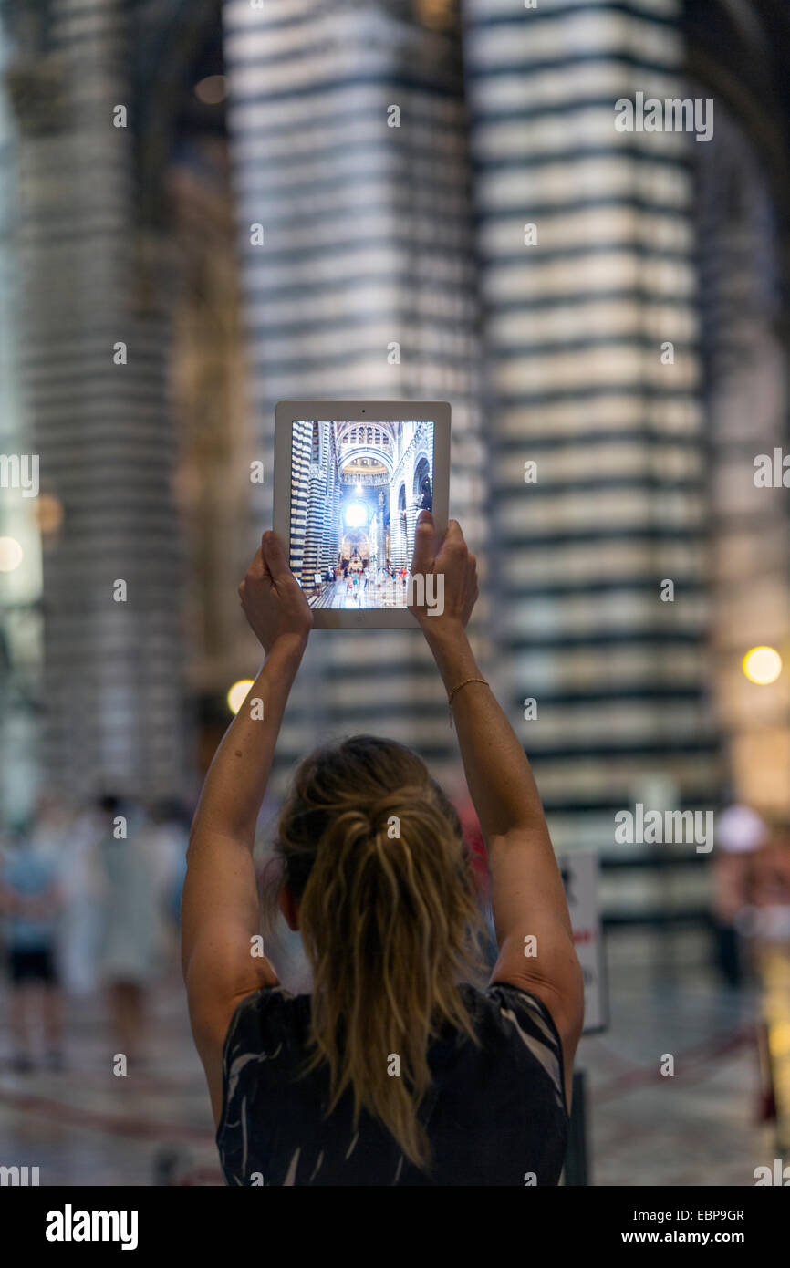 https://c7.alamy.com/comp/EBP9GR/woman-taking-a-picture-with-her-ipad-of-the-nave-of-siena-cathedral-EBP9GR.jpg