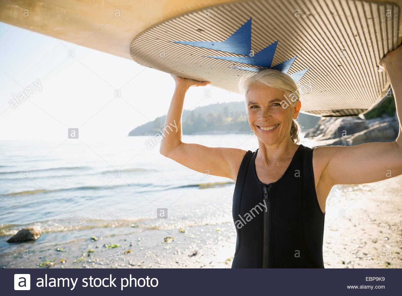 Senior woman holding paddle board overhead on beach - Stock Image