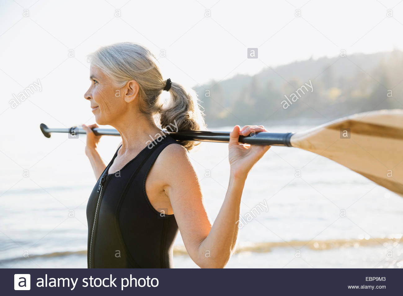 Senior woman holding paddle on sunny beach - Stock Image