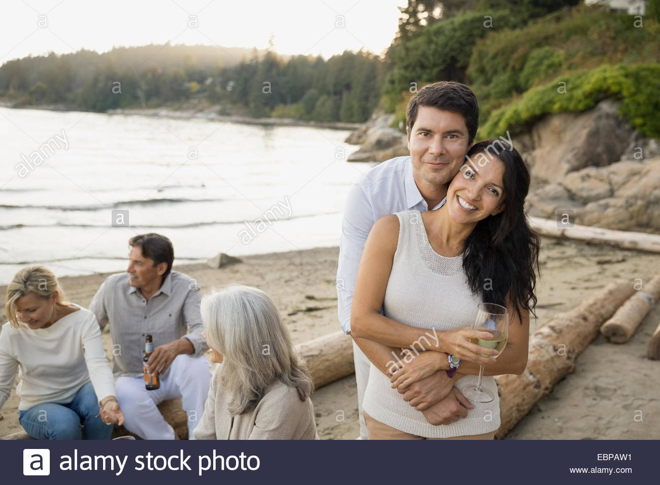 Portrait of smiling couple with friends on beach - Stock Image