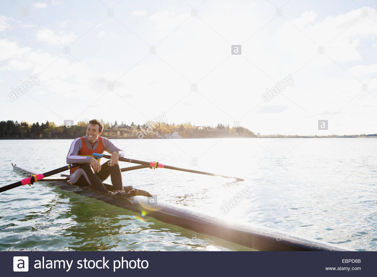 Smiling rower in scull on river - Stock Image
