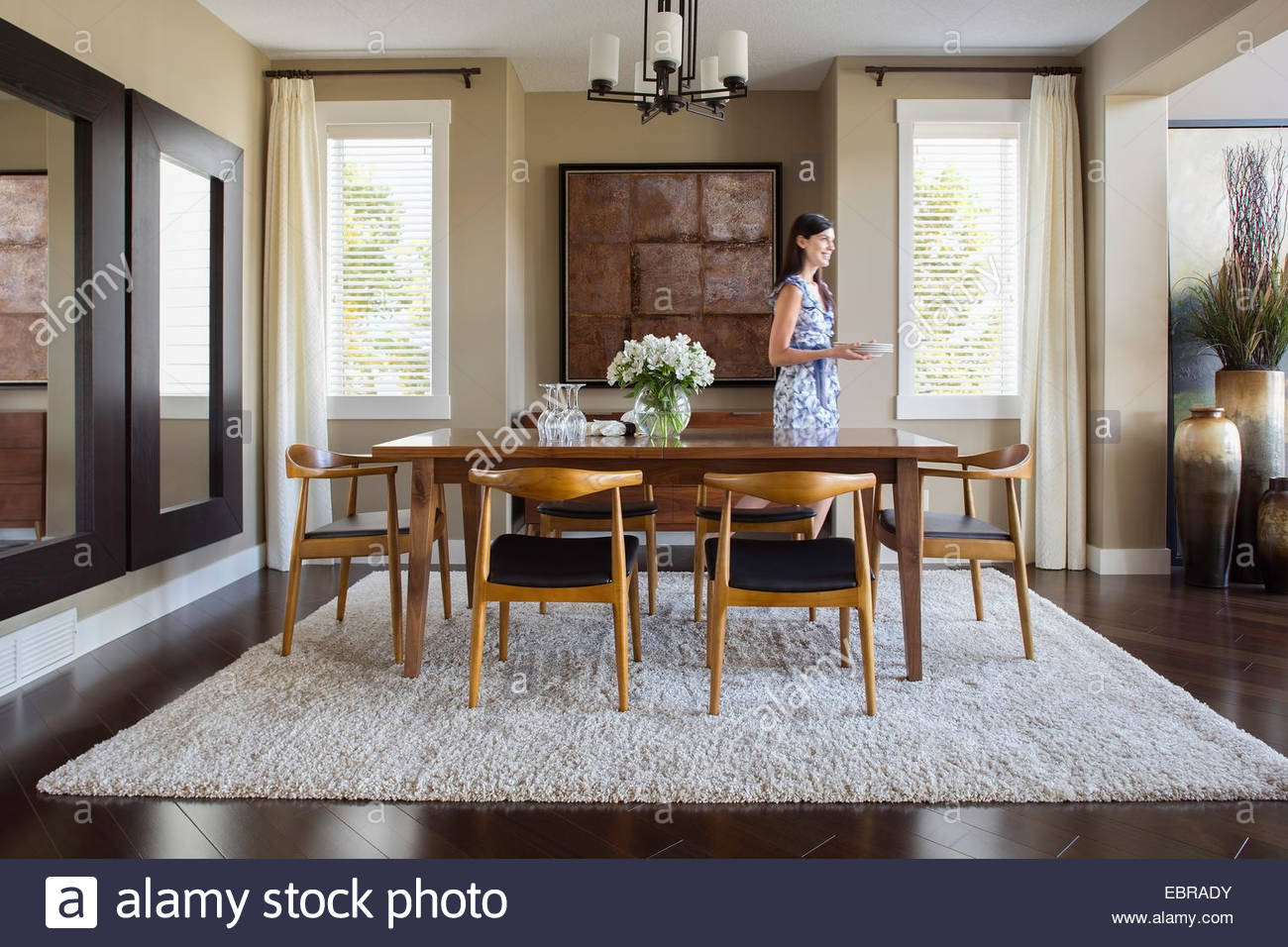 Woman setting table in dining room - Stock Image