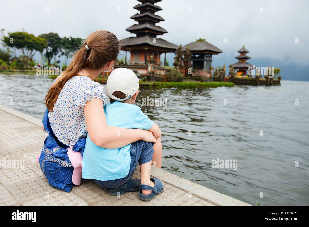 family enjoying views of beautiful Bali water temple at Bratan lake, Indonesia, Bali - Stock Image