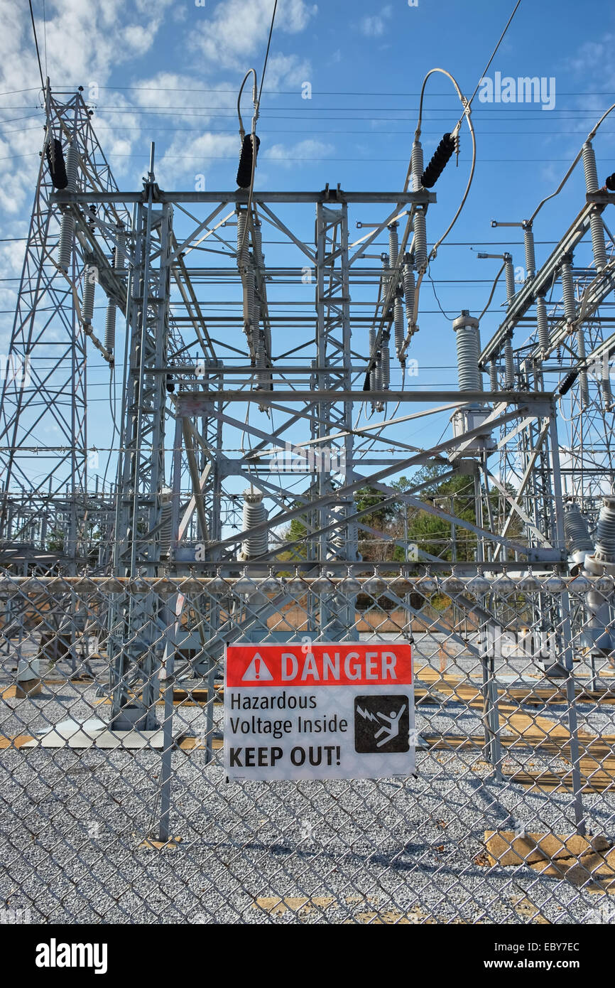 Danger sign warning of hazardous high voltage power lines and advising to keep out at electricity power transfer Stock Photo
