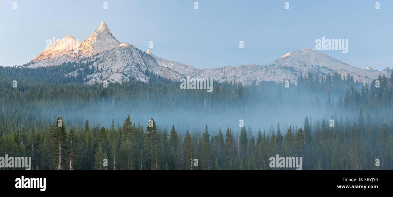 Unicorn Peak mountain above mist shrouded pine forest, Yosemite National Park, California, USA. Autumn (October) - Stock Image