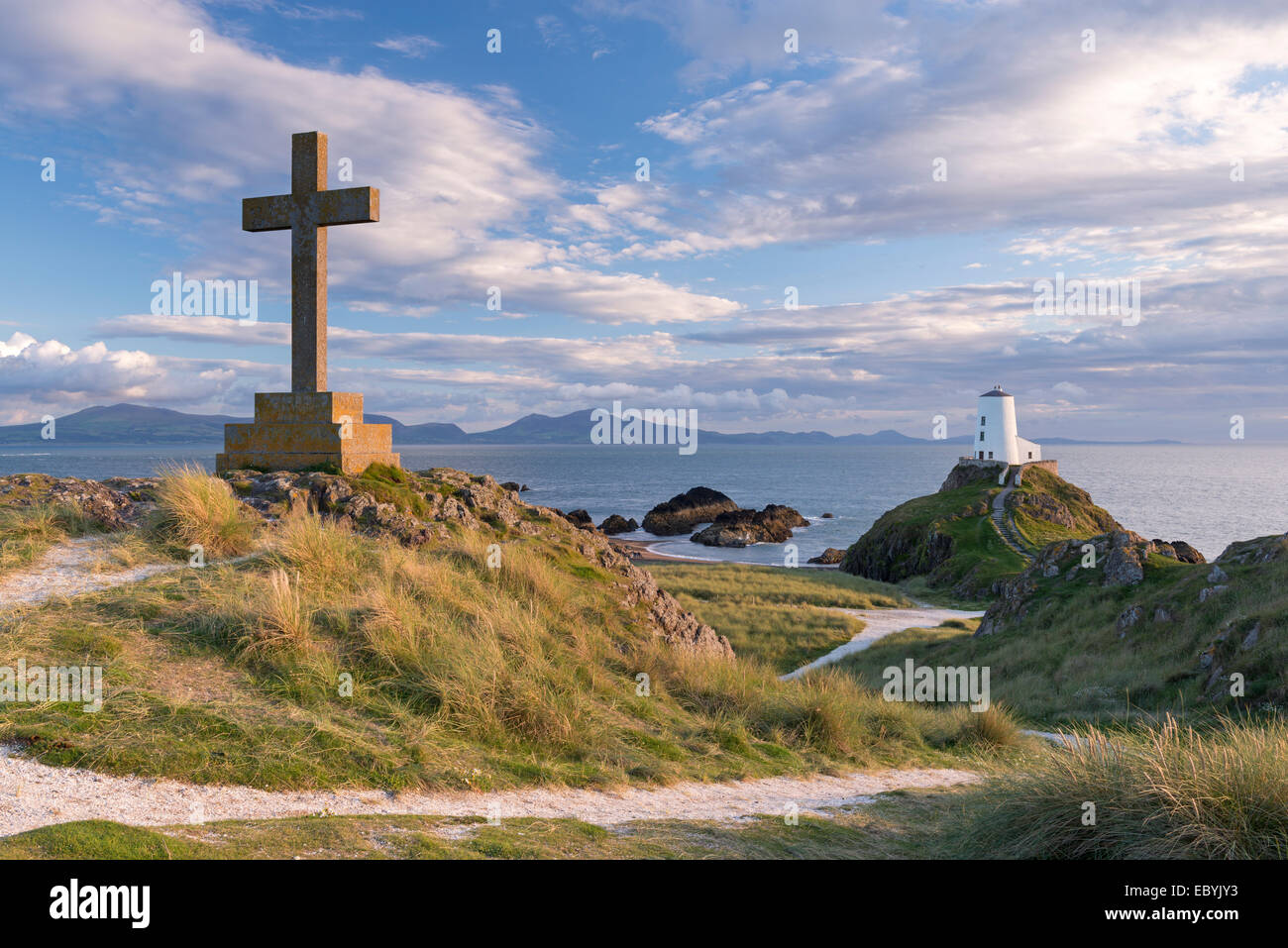 Cross and lighthouse on Llanddwyn Island, Anglesey, Wales. Autumn (September) 2013. - Stock Image