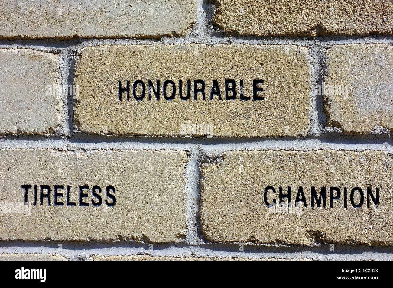 A brick with the words 'Honourable, Tireless and Champion' carved into it. - Stock Image