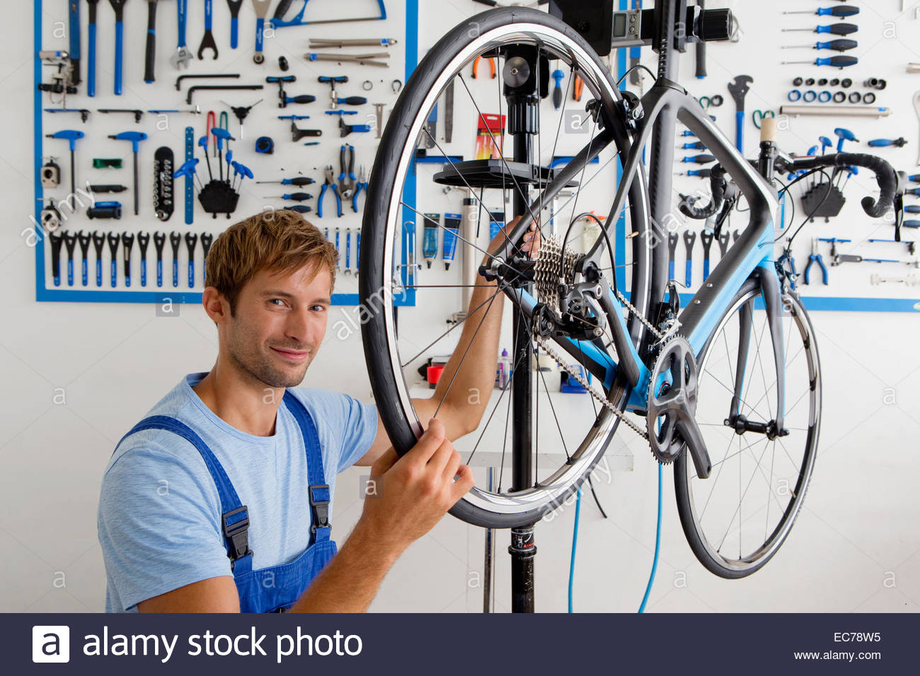 Cycle technician looking at camera in workshop - Stock Image