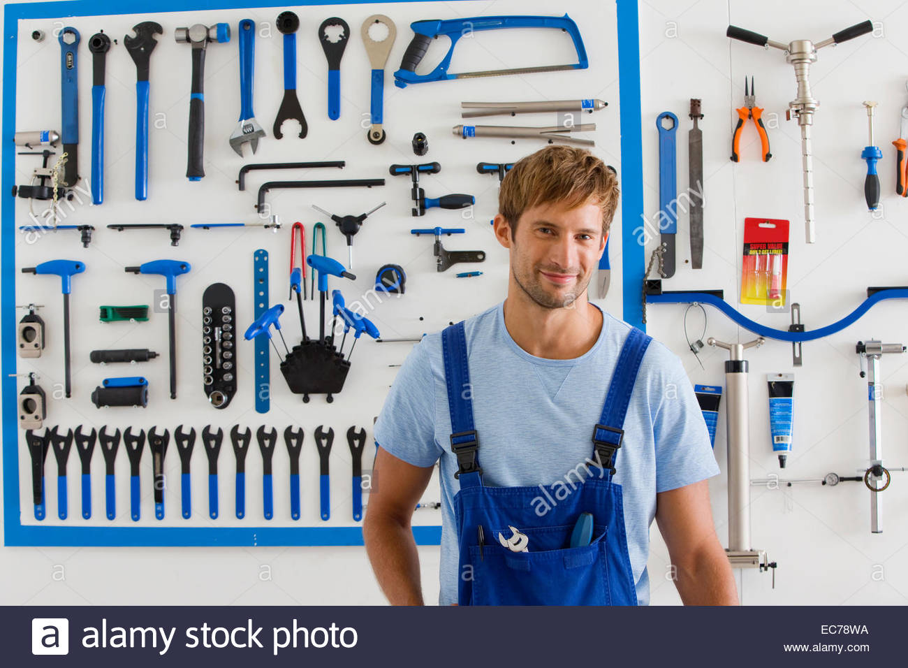 Cycle technician in workshop looking at camera - Stock Image