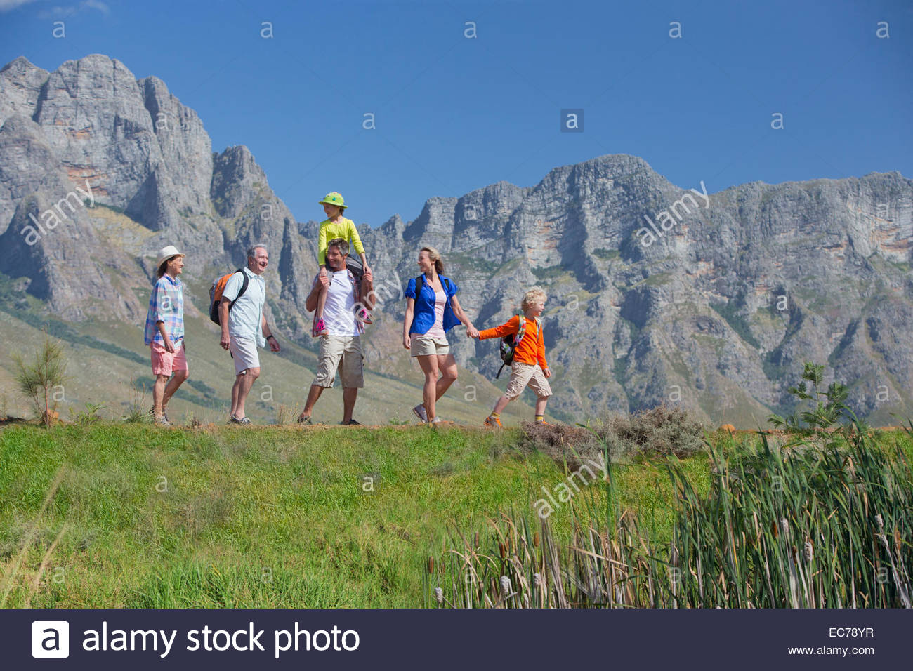 Multi generation family hiking on mountain path - Stock Image
