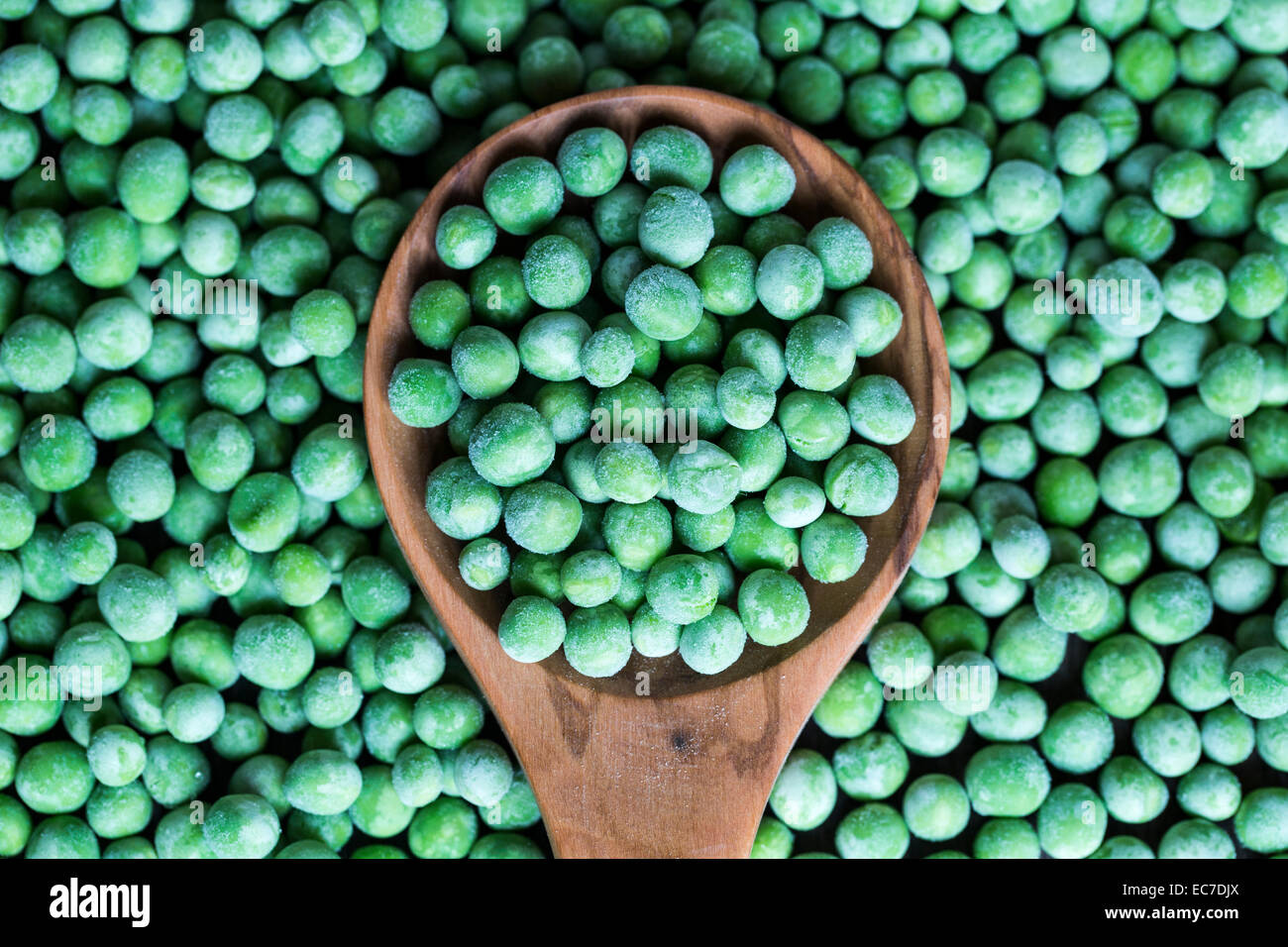 Wooden spoon and frozen peas Stock Photo