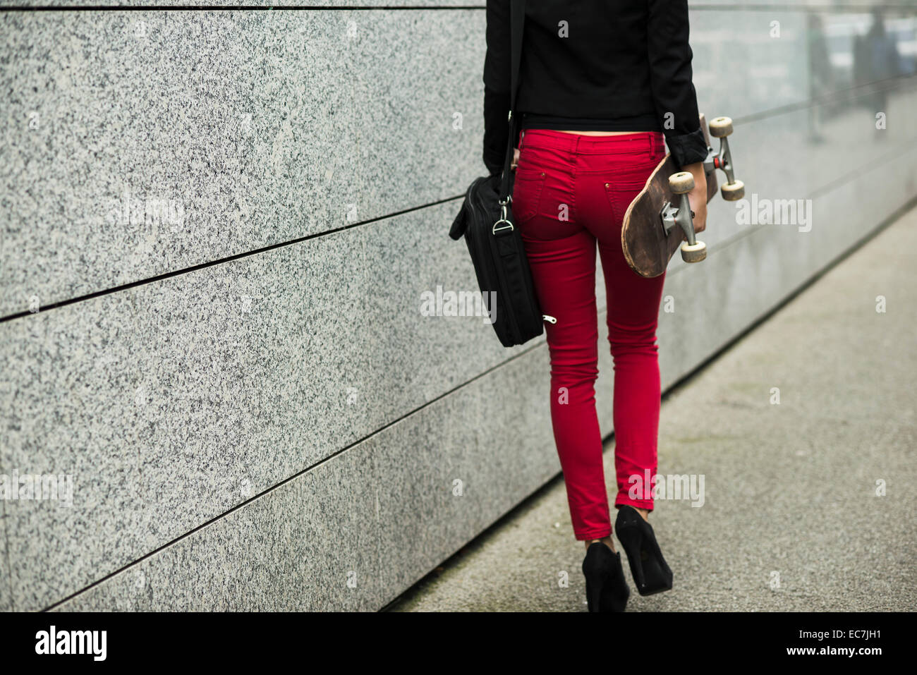 Young woman with bag and skateboard wearing red trousers, partial view - Stock Image