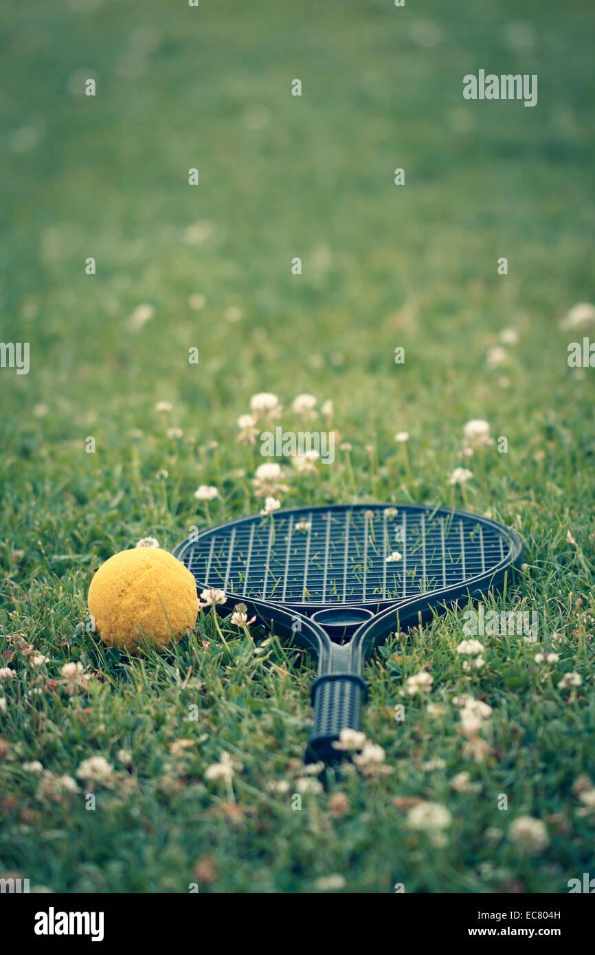 plastic tennis racket, yellow ball on grass - Stock Image