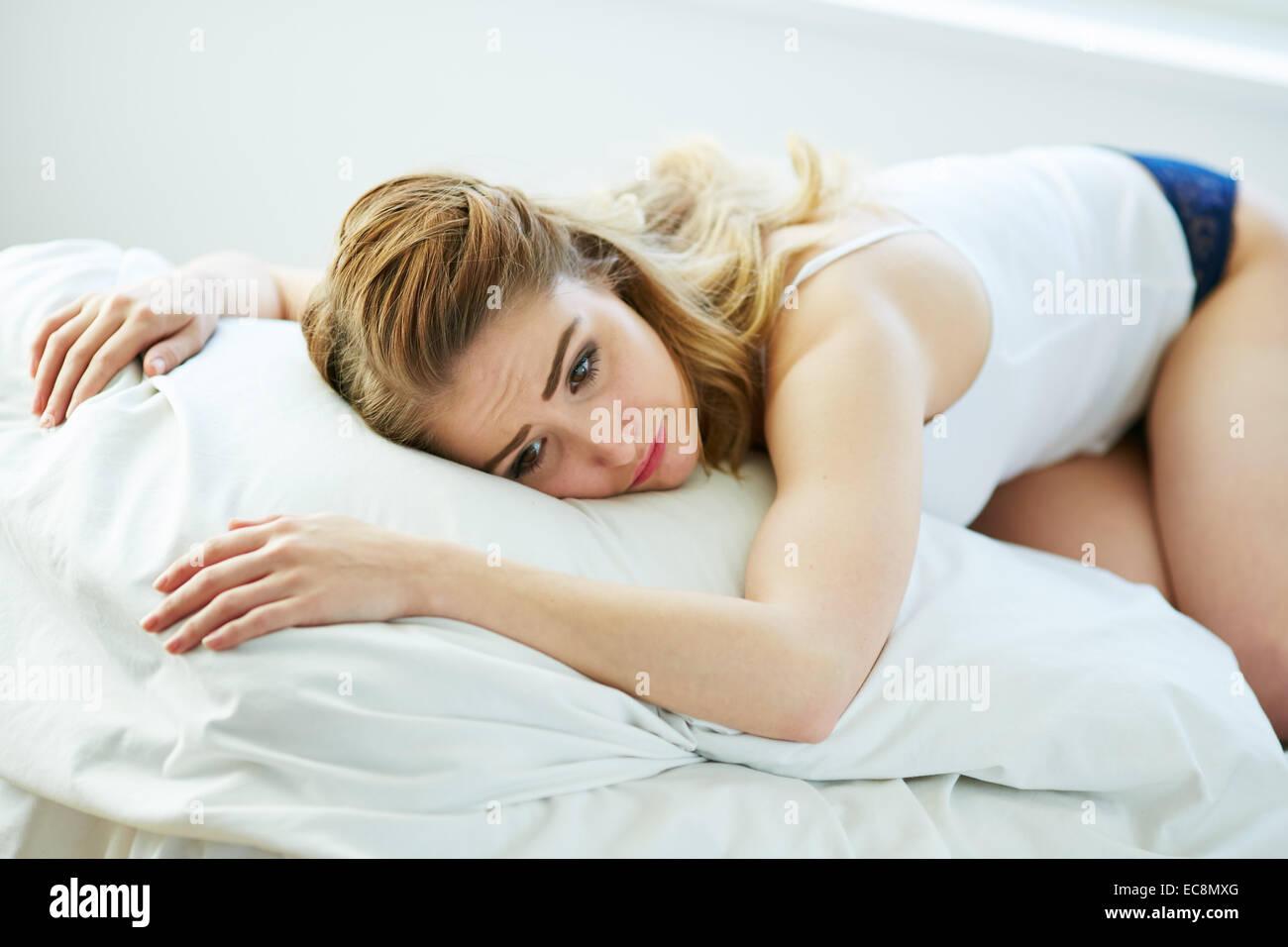 Upset girl lying on bed - Stock Image