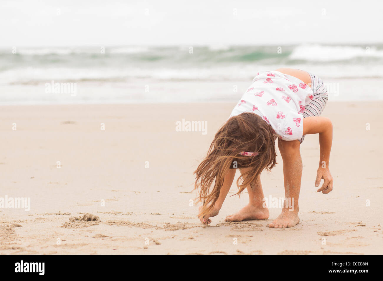 Girl (4-5) drawing in sand - Stock Image