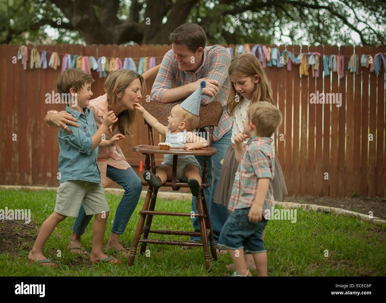 Family celebrating baby boys' first birthday in back yard - Stock Image