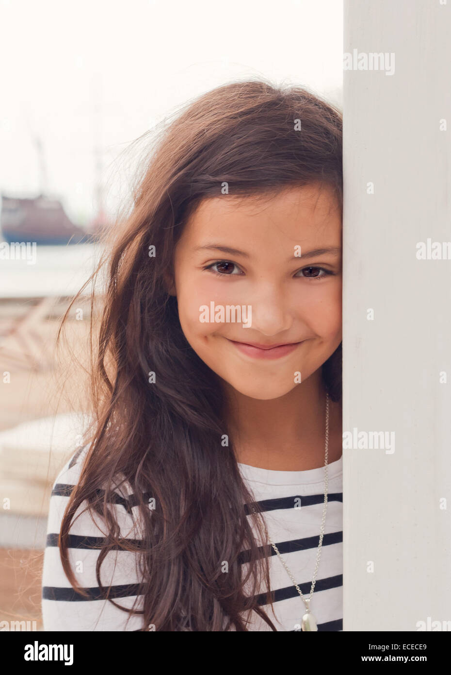 Pretty little girl (6-7) in striped dress smiling on beach near sea - Stock Image