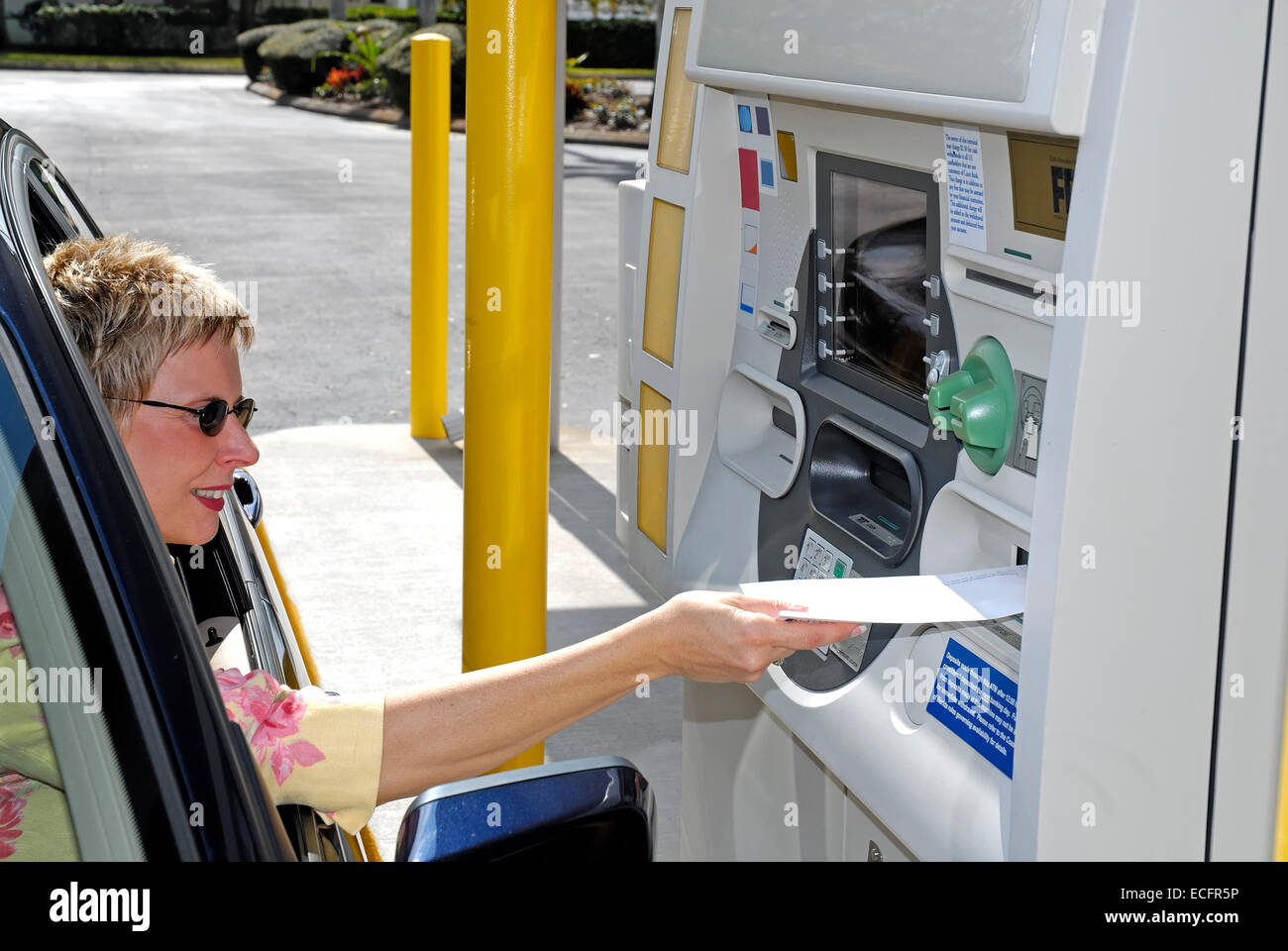 Mature Caucasian woman in a car using a drive up ATM machine. Stock Photo