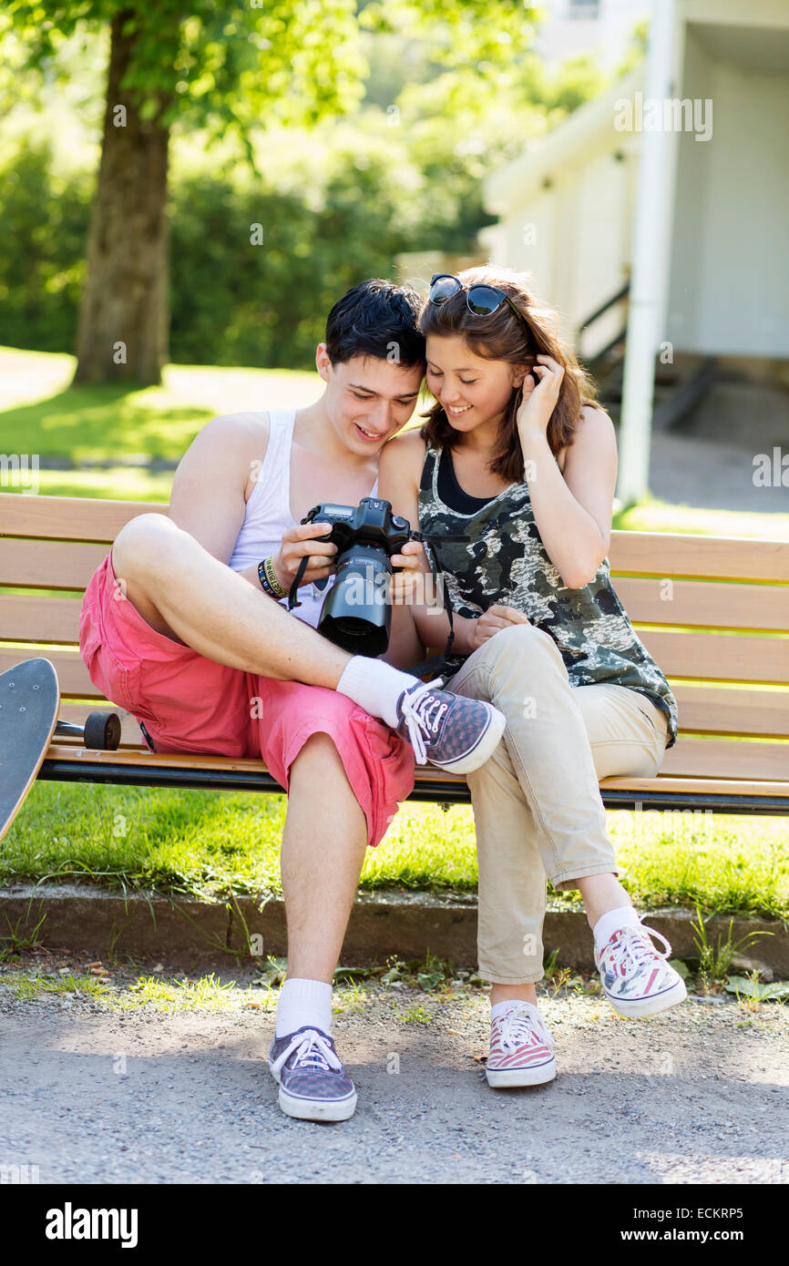 Happy couple looking photos on camera while sitting on bench in park - Stock Image