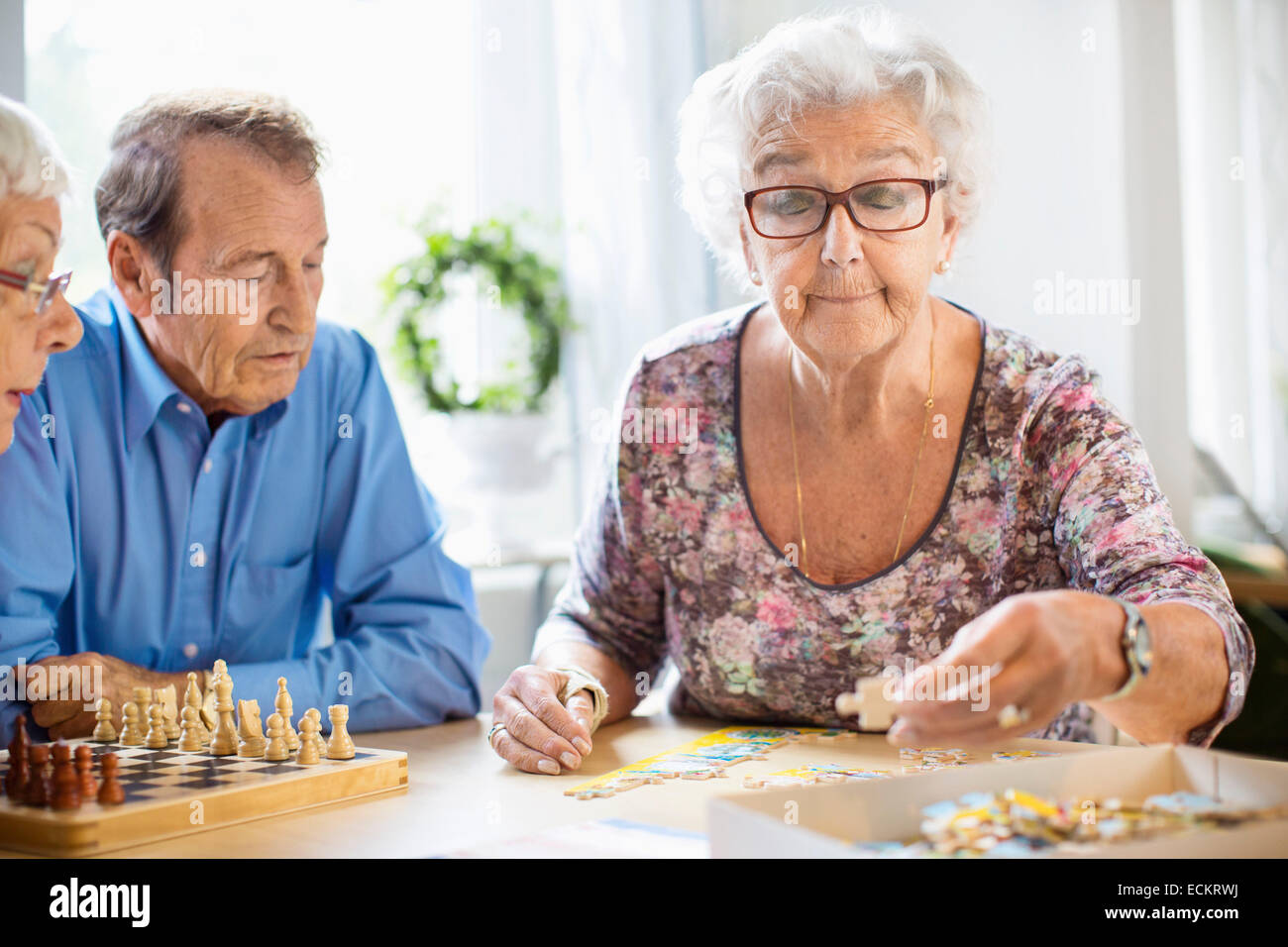 Senior people playing leisure games at table in nursing home - Stock Image