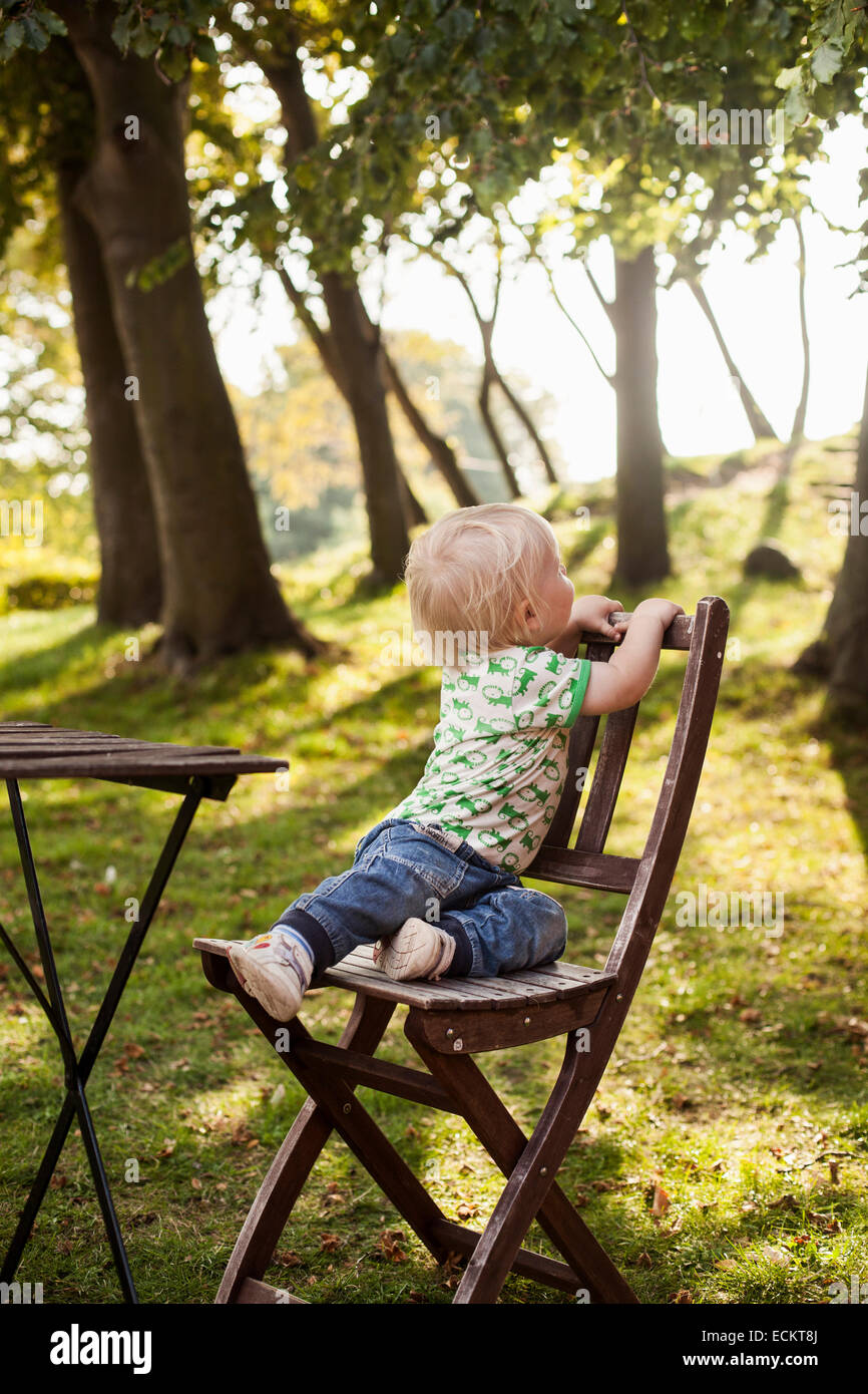 Full length of baby boy sitting on wooden chair in park - Stock Image