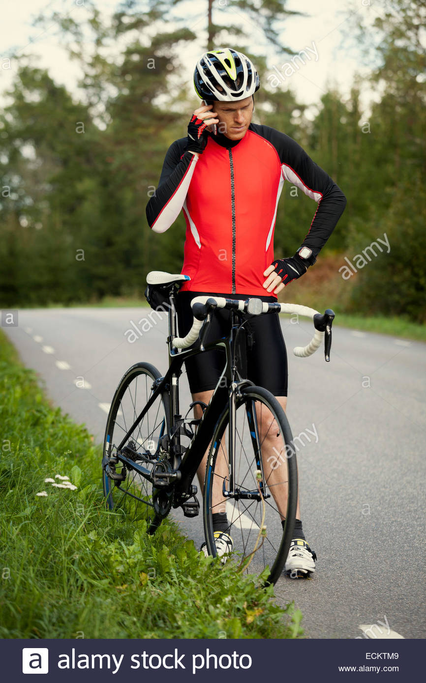 Full length of cyclist using mobile phone while standing by bicycle on country road - Stock Image