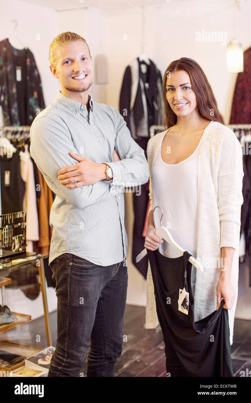Portrait of smiling male sales person with female customer in boutique - Stock Image