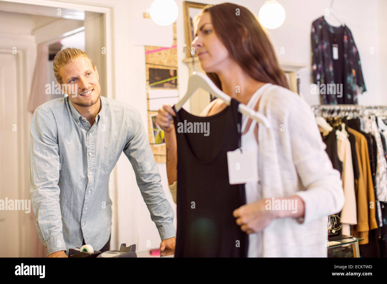 Male owner looking at female customer trying evening gown in ...