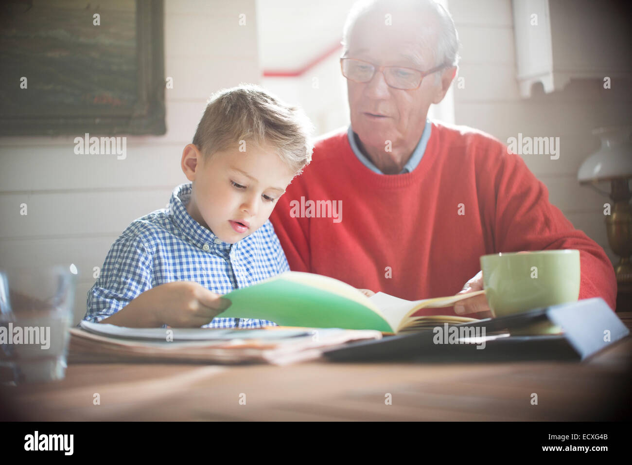 Boy reading with grandfather at table - Stock Image