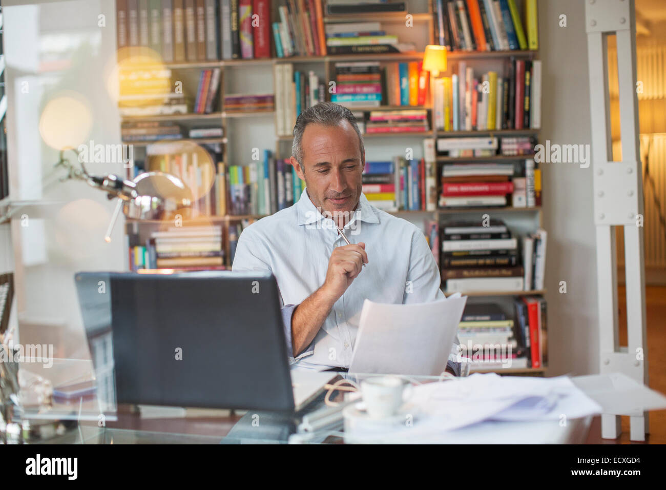 Businessman reading paperwork at home office desk - Stock Image