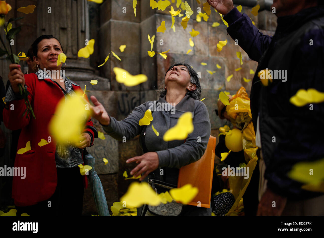 Beijing, Colombia. 22nd Apr, 2014. Residents play with papercuts of butterflies in front of the Primary Cathedral Stock Photo