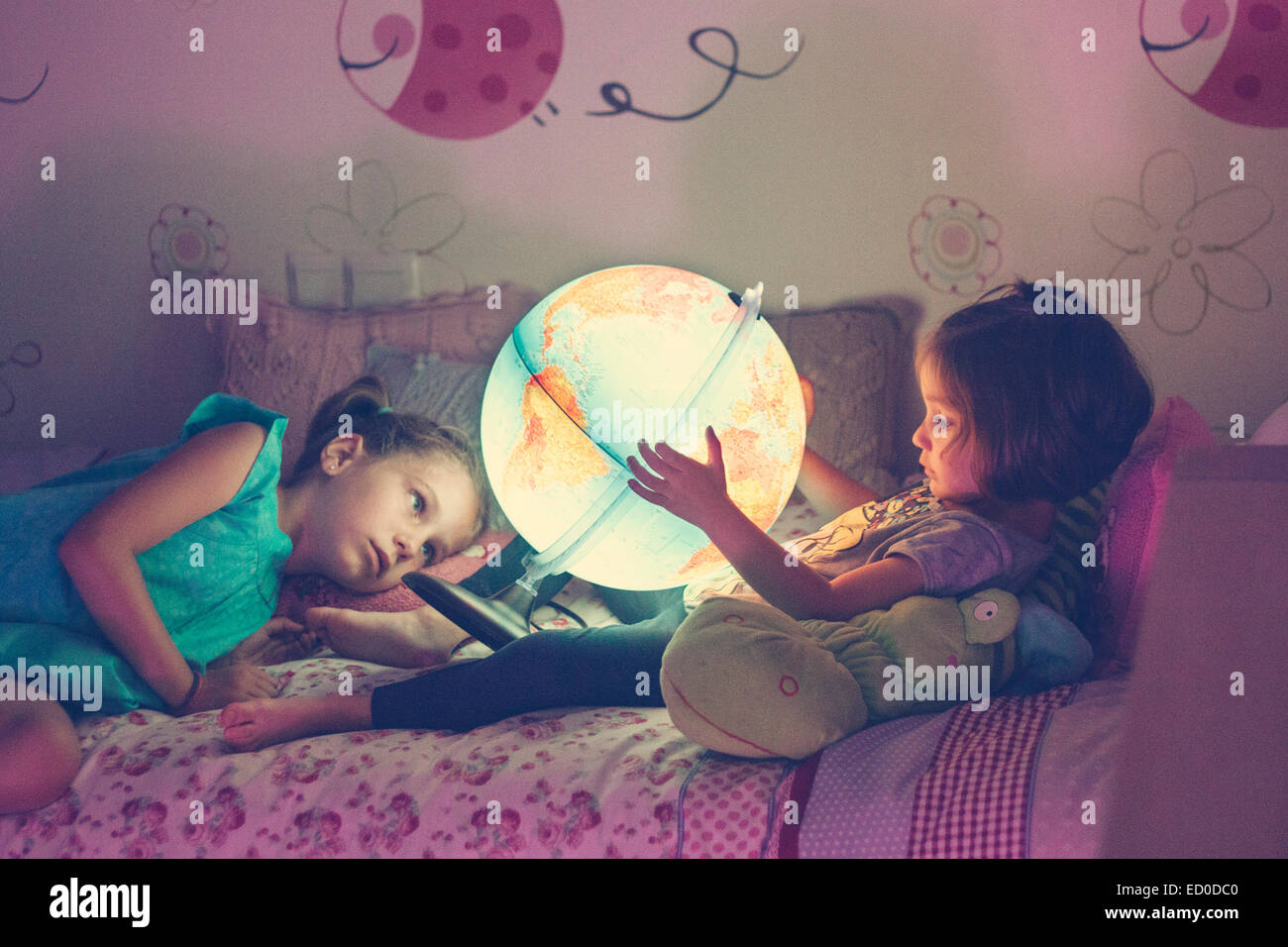 Two girls (2-3, 6-7) looking at illuminated lamp in shape of globe - Stock Image