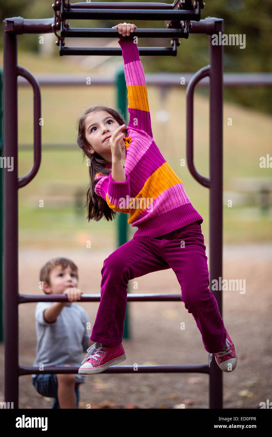 Girl and boy playing on climbing frame - Stock Image