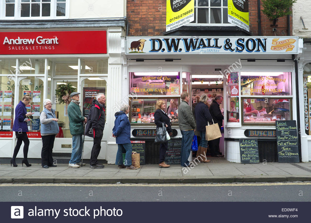 Ludlow, Shropshire, UK, Tuesday 23rd December 2014. Shoppers line up outside the butcher shop of D.W.Wall & Son, Stock Photo