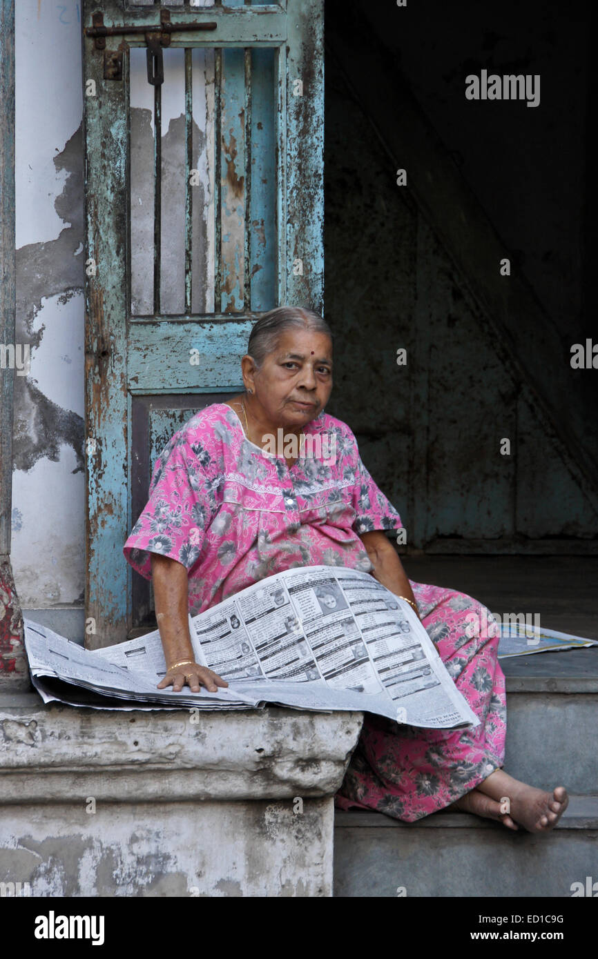 woman reading newspaper outside home in old ahmedabad, gujarat