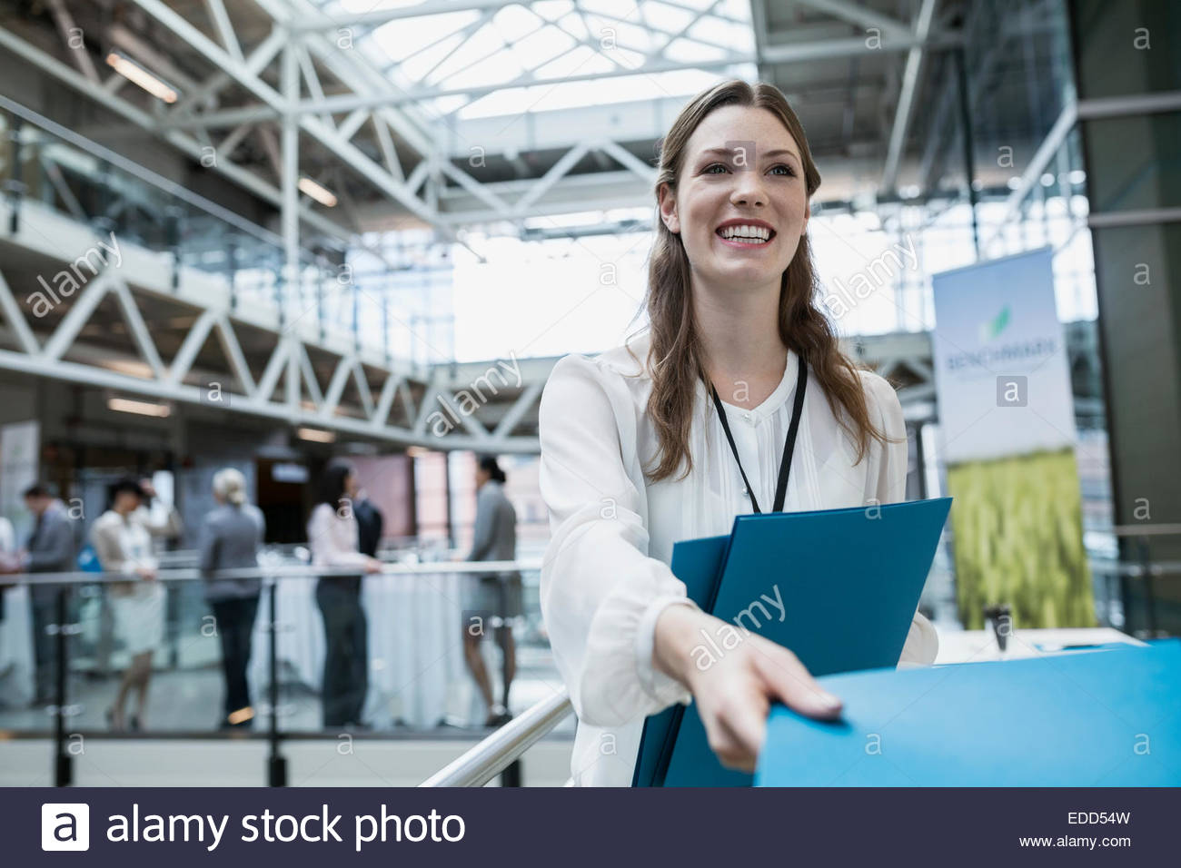 Businesswoman handing out folders at conference - Stock Image