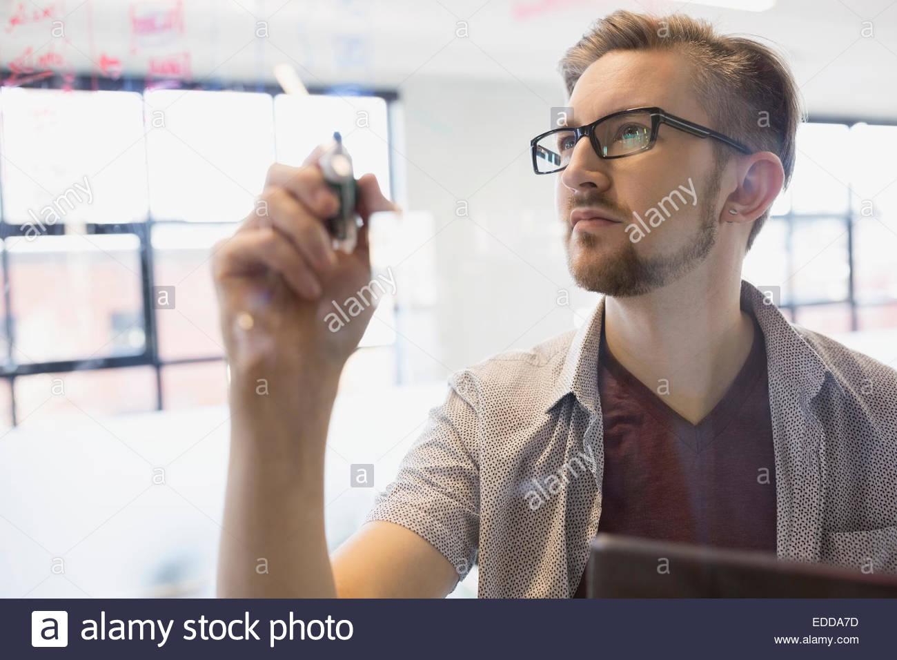 Businessman writing on glass - Stock Image