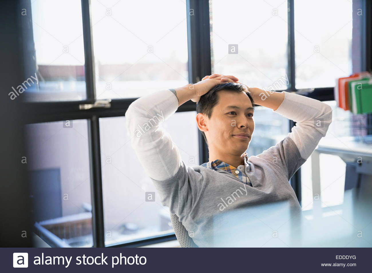 Casual businessman with hands behind head in office - Stock Image
