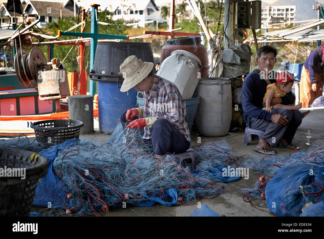 Role reversal with man caring for baby whilst woman tends the fishing nets. Thailand S. E. Asia. - Stock Image