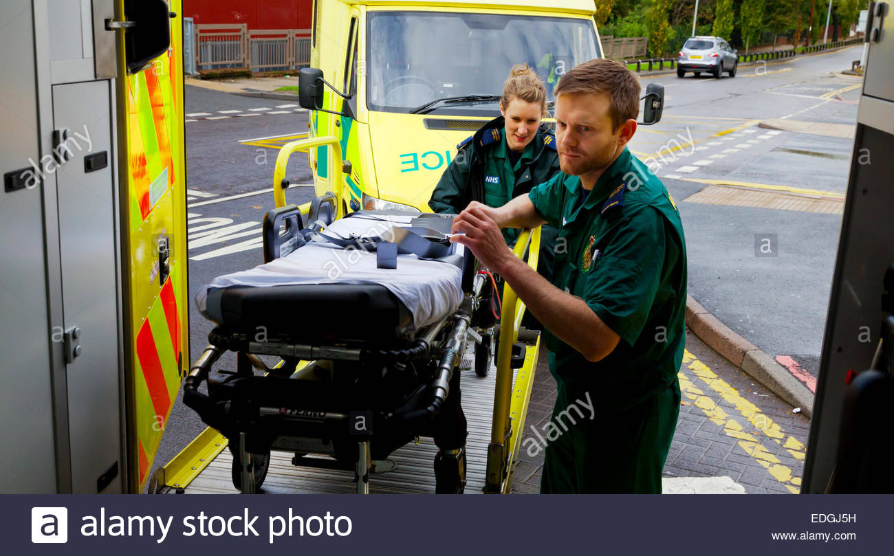 Male and female paramedics loading an empty stretcher trolley into an NHS Ambulance in north west England UK - Stock Image