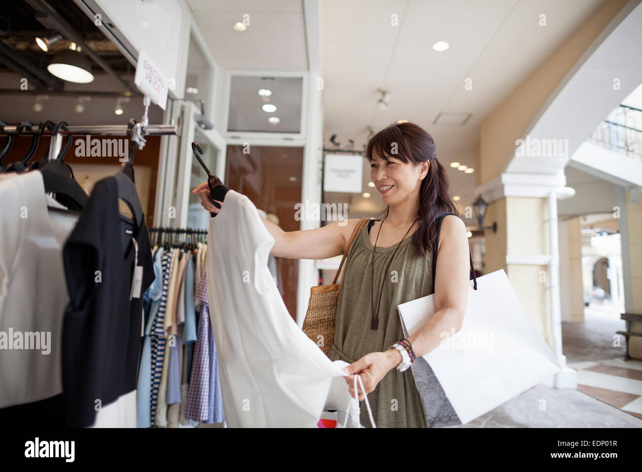 Woman looking at clothing in a shopping mall. - Stock Image