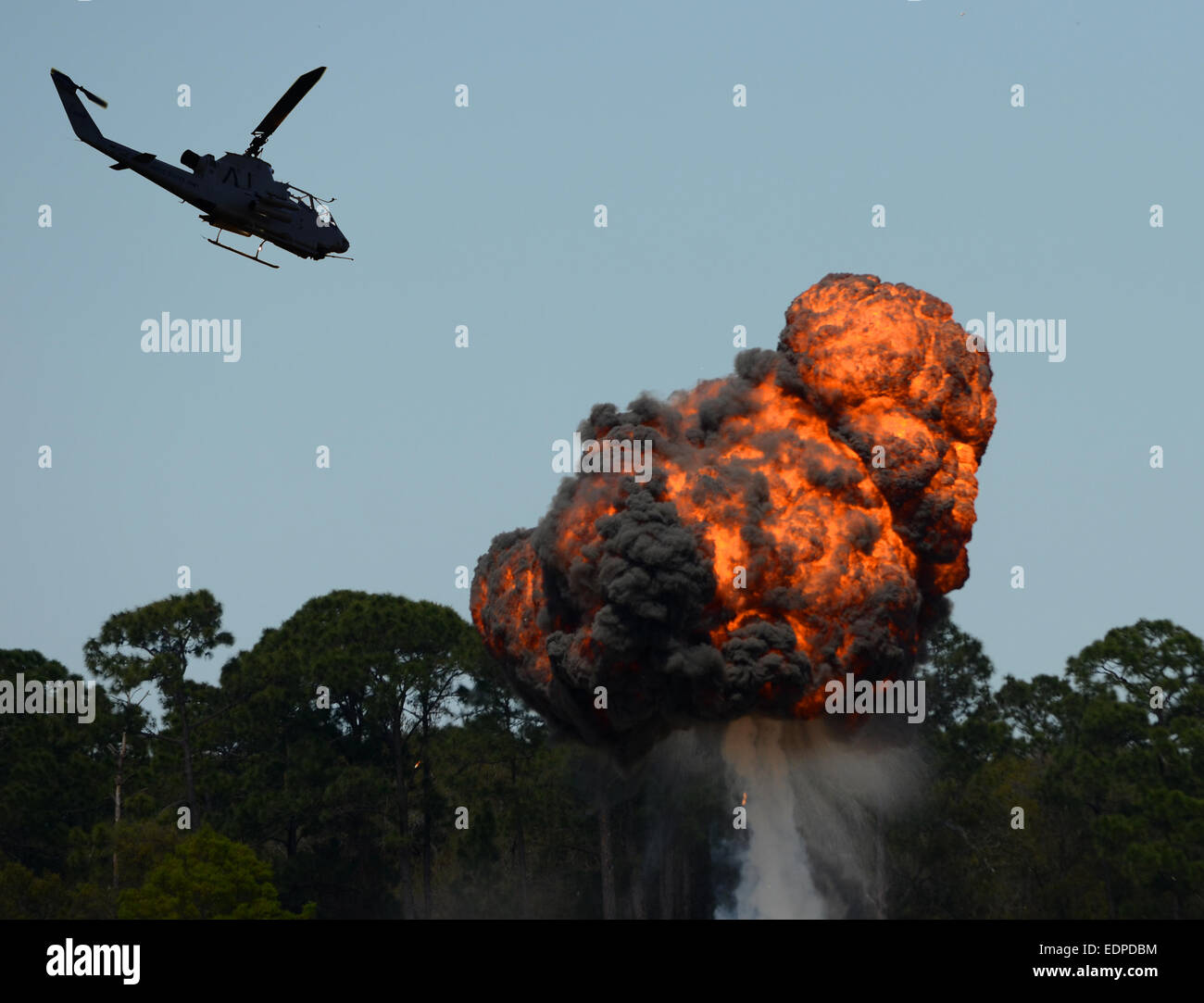 Military helicopter flying over fiery explosion and fireball - Stock Image