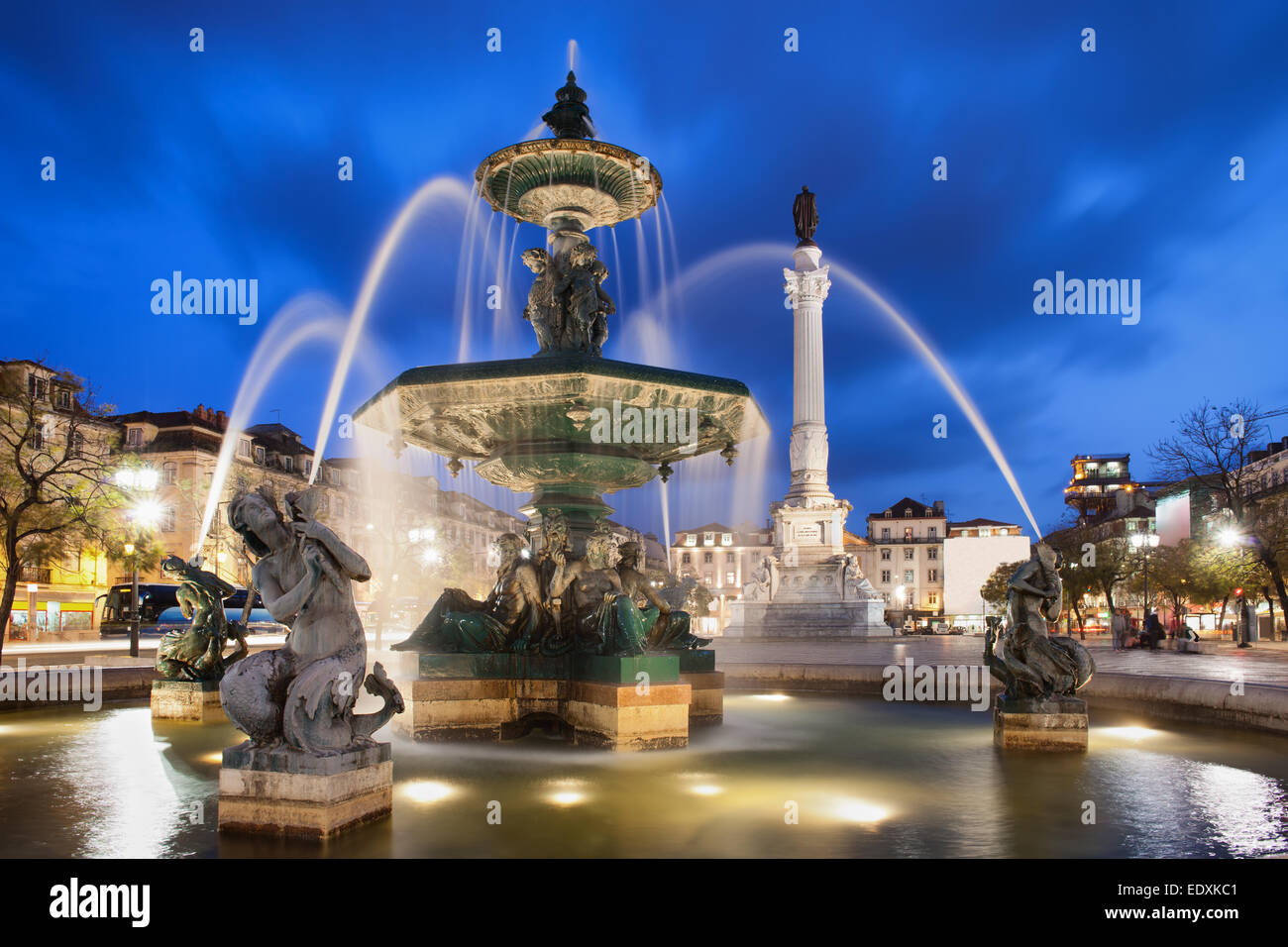 Fountain on Rossio Square at night in Lisbon, Portugal. Baroque style artwork with mythical creatures sculptures. - Stock Image