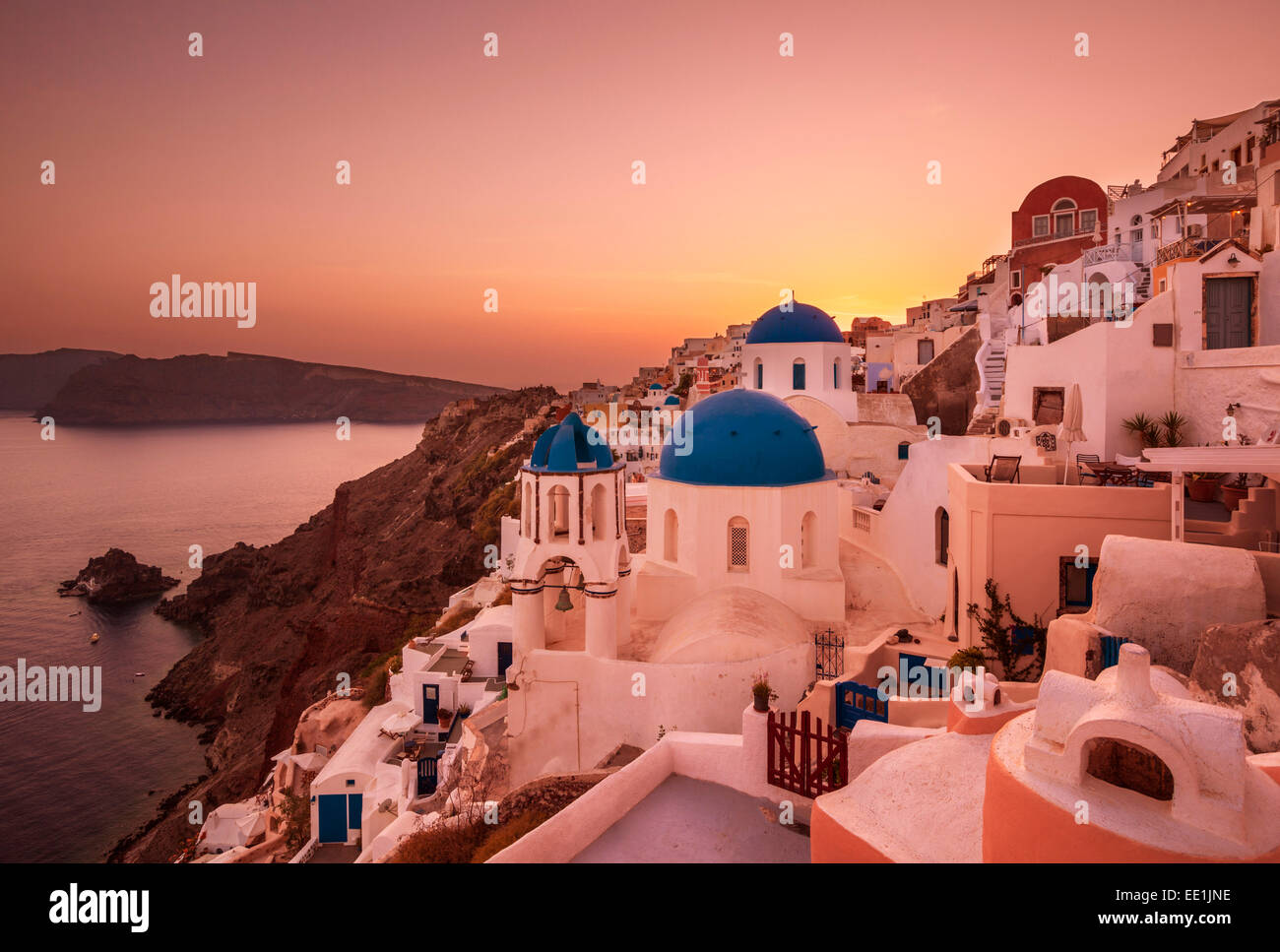 Greek church with three blue domes at sunset, Oia, Santorini (Thira), Cyclades Islands, Greek Islands, Greece, Europe - Stock Image